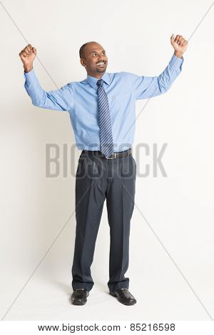 Full body Indian businessman hand celebrate and looking up at blank copy space, standing on plain background with shadow