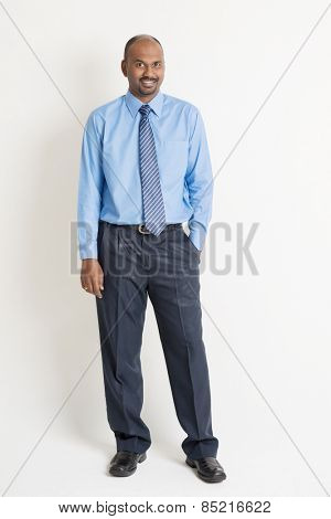 Full body Indian businessman standing on plain background with shadow