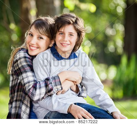 Portrait of happy mother embracing son at campsite