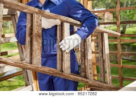 Midsection of worker carrying ladder at construction site