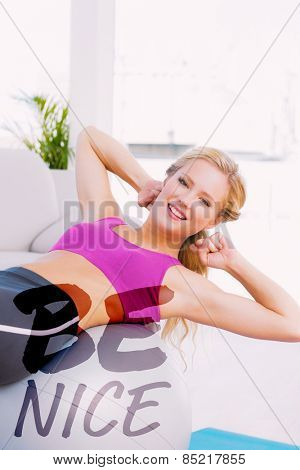 Smiling fit blonde doing sit ups with exercise ball against be nice