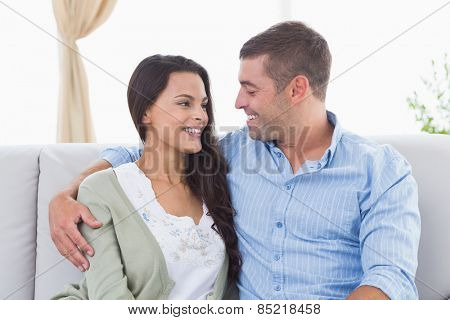 Happy romantic couple looking at each other while sitting on sofa at home