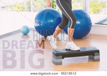 Low section of a fit woman performing step aerobics exercise against dream big