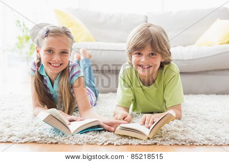 Portrait of happy siblings holding books while lying on rug in living room