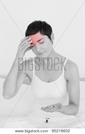 Woman having a headache in her bedroom