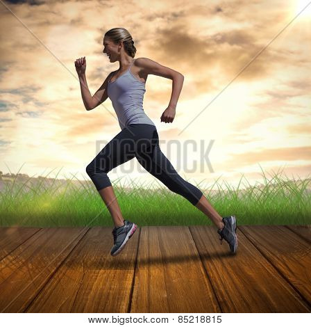 Pretty fit blonde jogging against wooden planks against field