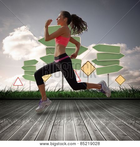 Full length of healthy woman jogging against road signs over wooden planks