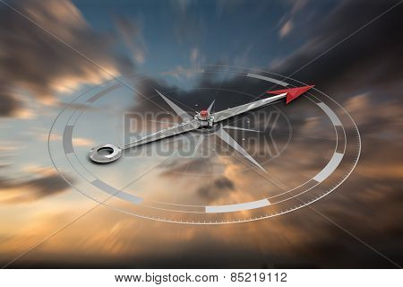 Compass against blue and orange sky with clouds