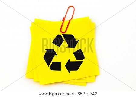 Recycling symbol against sticky note with red paperclip
