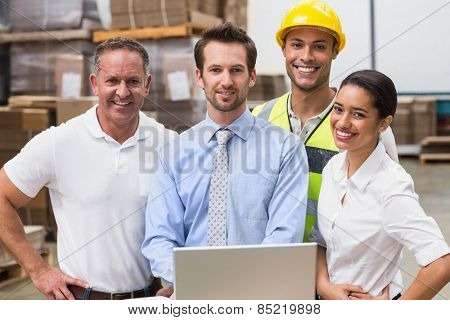 Warehouse managers and worker smiling at camera in a large warehouse