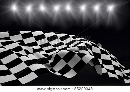 Checkered flag against football pitch at night with lights