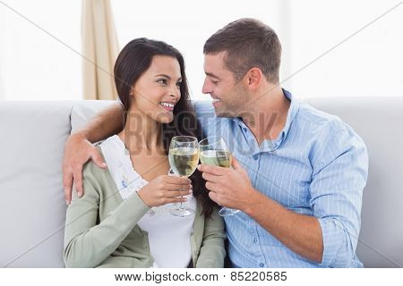 Happy loving couple toasting wine glasses at home