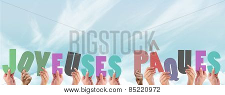 Hands holding up joyeuses pasques against blue sky