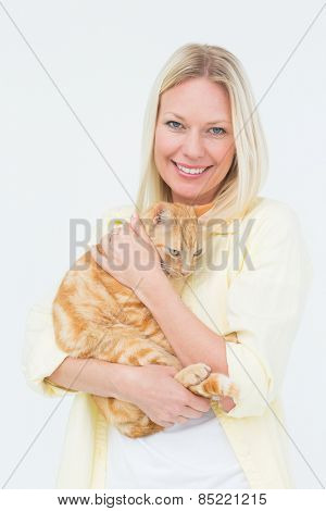 Portrait of beautiful woman holding cat on white background