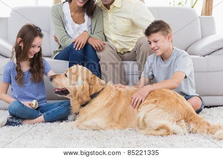 Happy siblings stroking dog while father and mother sitting on sofa at home