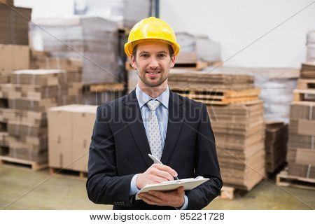Smiling warehouse manager writing on clipboard in warehouse