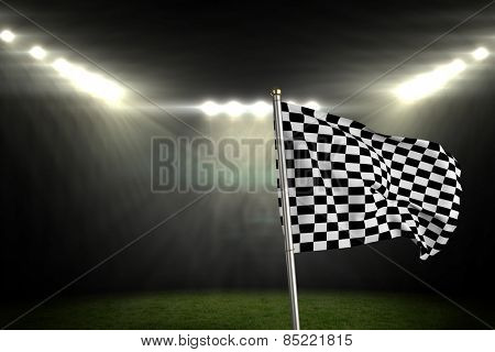 Checkered flag against football pitch under bright spotlights