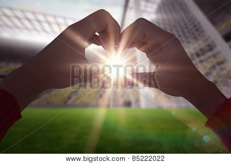 Woman making heart shape with hands against football stadium