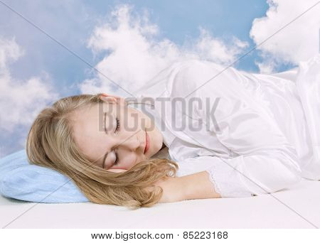 Sleeping young woman on the sky background.