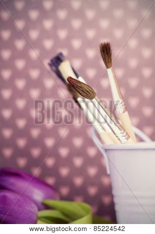 Retro styled photo of paintbrushes and purple tulips