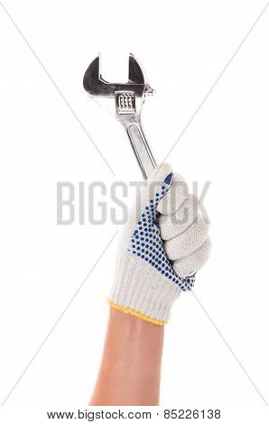 Hand in gloves holding adjustable wrench.