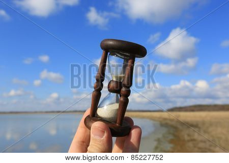 Hourglass in man hand on sky background
