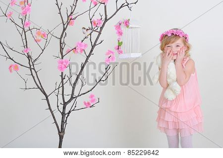 Girl In A Pink Wreath And A Pink Dress With A Bird On A Flowering Tree. Laughing And Holding Her Che