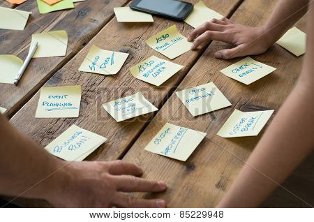 Businessman and woman leaning on desk with various sticky note papers