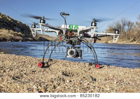 WILDCAT, CO, USA, March 9,  2015:  DJI F550 Flame Wheel  hexacopter drone landing with a camera on river shore.