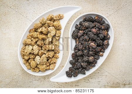 black and white mulberry - sun-dried fruit on teardrop shaped bowls against rustic barn wood