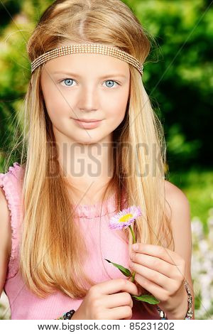 Portrait of a beautiful teenage girl in the summer park. Holiday.