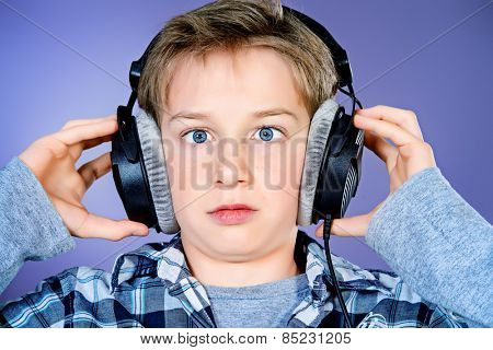 Funny teen boy listening to music in headphones. Studio shot.
