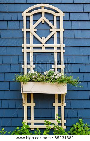 A decorative flower planter and trellis on the side of an older style home.