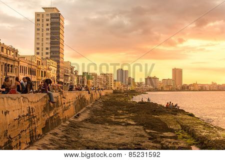 HAVANA,CUBA - MARCH 5, 2015 : Cubans sitting on the Malecon seawall during a beautiful sunset