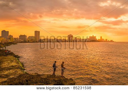 HAVANA,CUBA - MARCH 5, 2015 : Sunset in Havana with two unidentified fishermen on the foreground