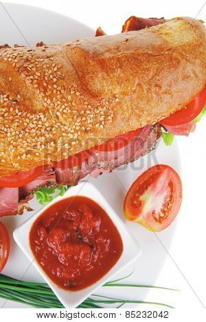 french sandwich on white plate: long baguette with smoked chicken sausage and chives isolated on white background
