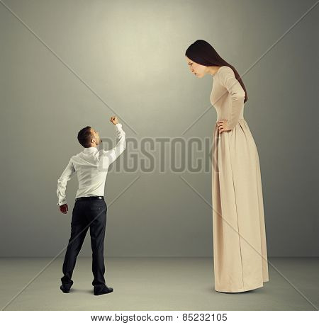 small angry man showing fist to dissatisfied woman in long dress over grey background