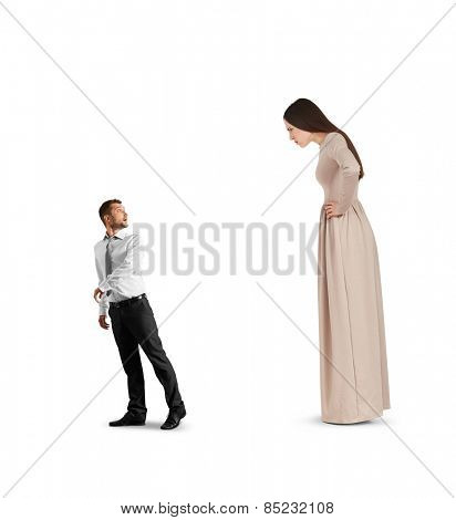 discontented woman in long dress staring at outgoing small man. isolated on white background