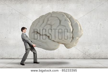 Businessman making effort to carry huge human brain
