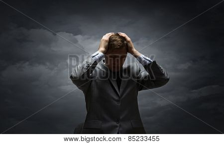 Young troubled businessman with hands on his head