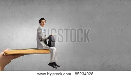 Young man sitting on old opened book