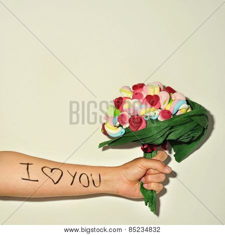 a young man offering a candy bouquet and the sentence I love you written in his forearm