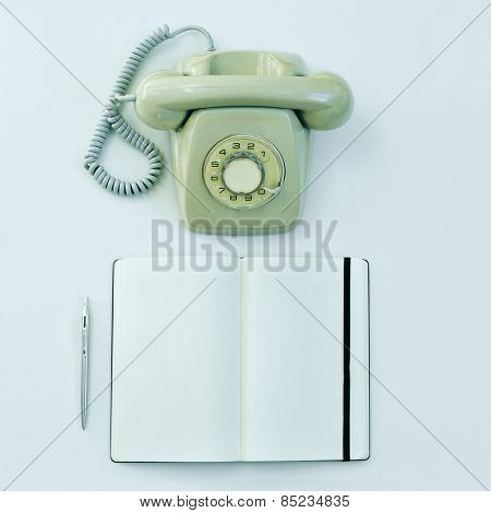 high-angle shot of a rotary telephone, a pen and a blank notepad on a table