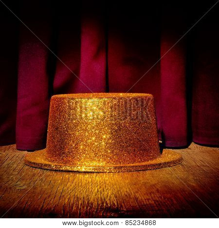 a golden top hat on a stage with the theater curtain in the background