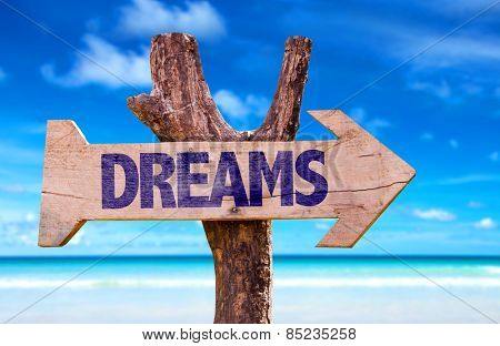 Dreams wooden sign with beach background