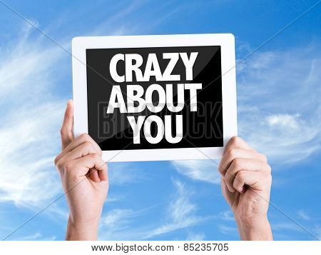 Tablet pc with text Crazy About You with sky background