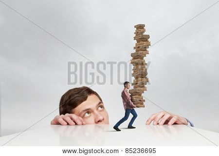 Young businessman looking from under table at man carrying pile of books
