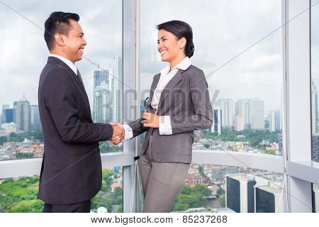 business people handshake to seal deal in front of city skyline