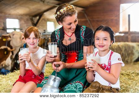 Bavarian mother sitting with children in cowhouse on hay bale drinking fresh milk