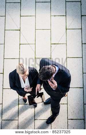 Business man and woman  with tablet computer standing on square, seen in top view